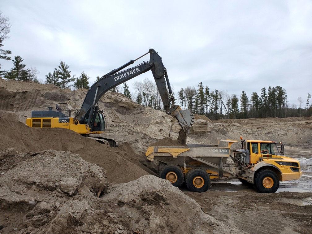 Excavator filling dump truck